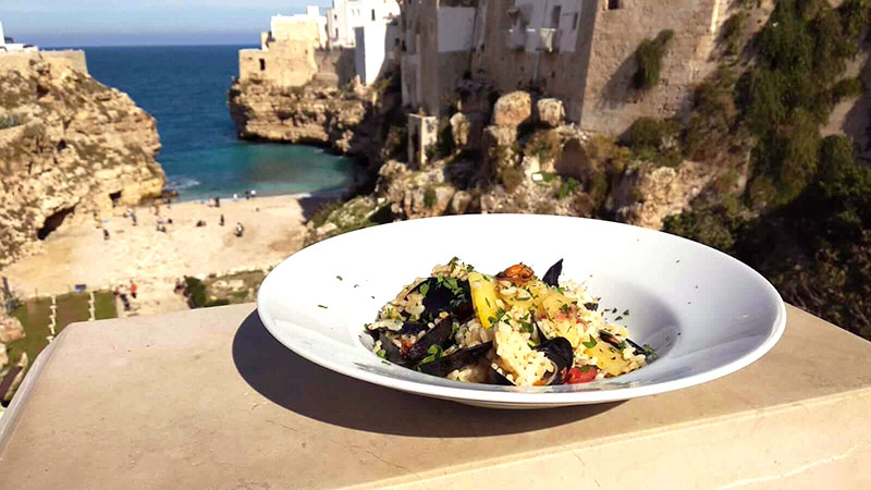 seafood dish with the village of polignano in the background cliffs and seaside beach