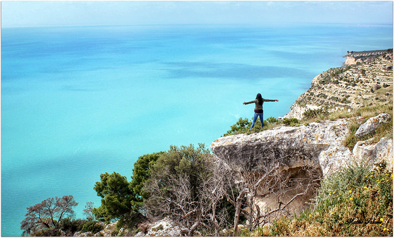 girl standing on cliff with arms wide open and an endless bright blue sea in front of her